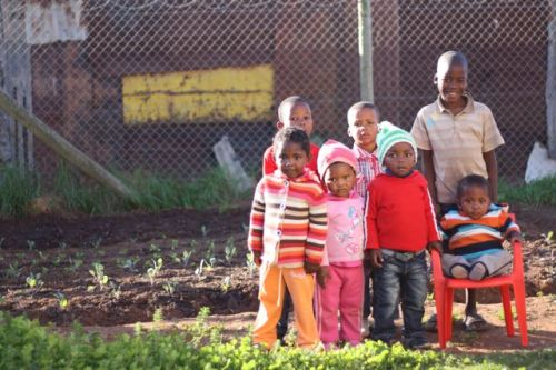 a few of the kids from the preschool posing with their new garden.